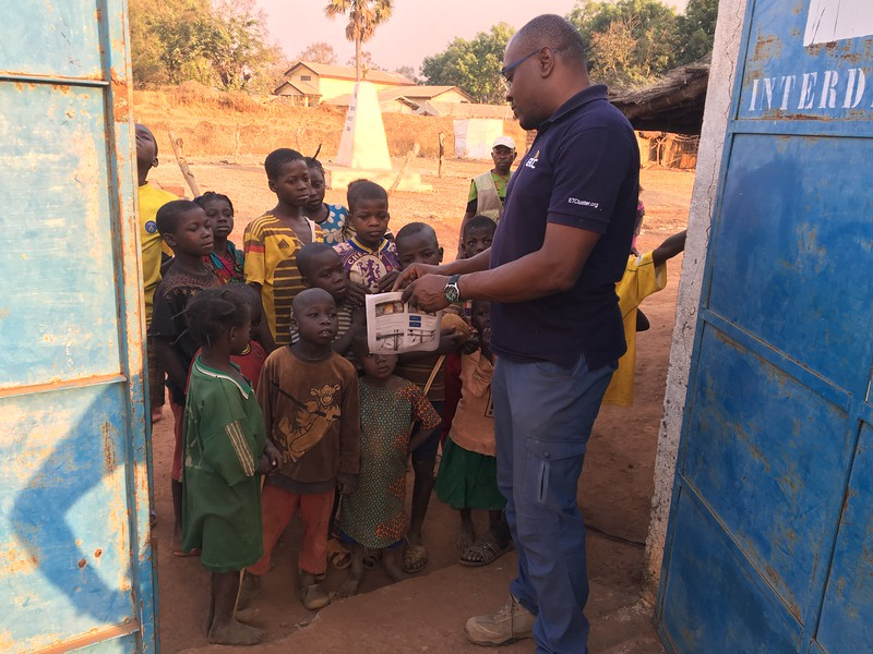 ETC representative Sylvain Tiako explains security communications to a group of children in Batangafo, Central African Republic, in January. Photo: WFP